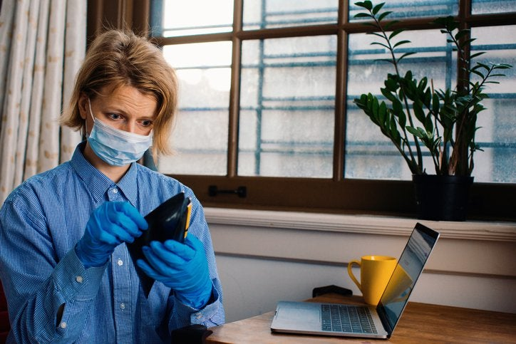 Woman in mask and gloves looks into empty wallet.