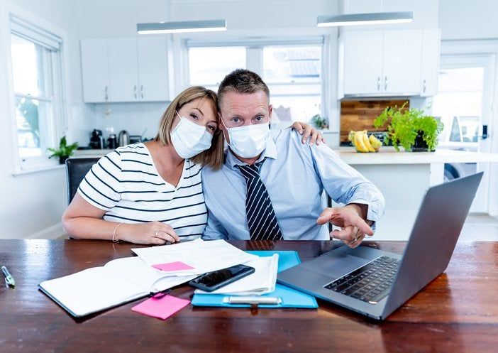 Masked couple at table with documents and computer.