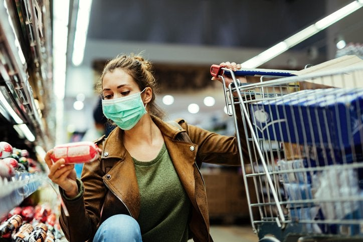 Woman wearing a mask examines groceries with one hand on her cart.