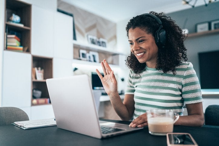 A woman works from home as she smiles and waves to a video call on her laptop.