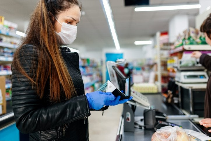 Woman at checkout ready to pay for groceries with credit card.jpg