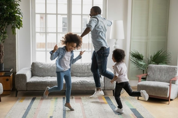 Man and kids dance around new home.