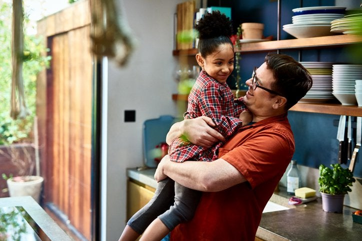 Parent holds their young child up in their kitchen. Both smile.