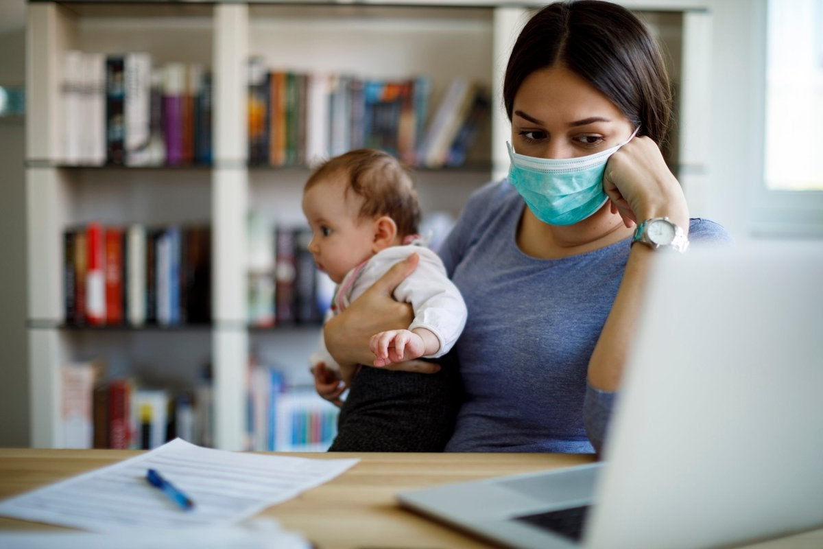 A worried caregiver wearing a face mask works from home while holding a baby.