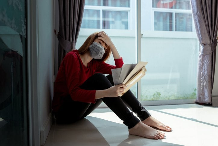 Masked woman sits on floor holding handful of bills in one hand and her head in the other.