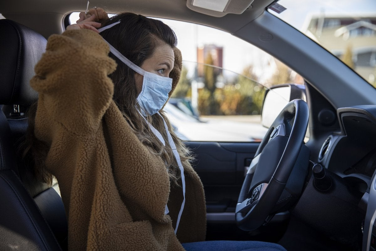 A person sits in the driver's seat of a parked vehicle and puts on a facemask.