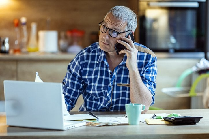 Worried man listens to a phone call while sitting in front of a laptop, calculator, and paperwork