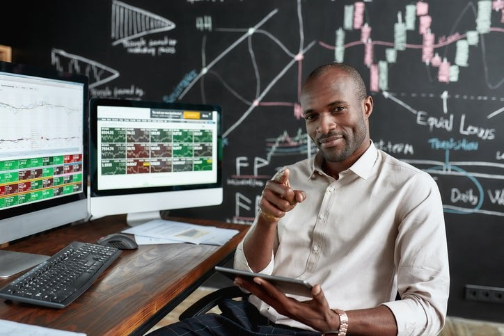 Man at desk with stocks and shares information smiles and points at camera.