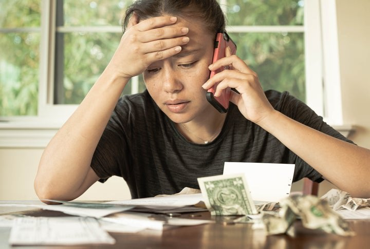 Stressed woman holding phone looks at bills.