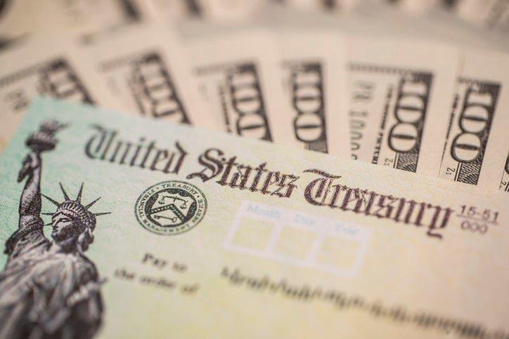 $100 bills surround a stimulus check from the U.S. Treasury