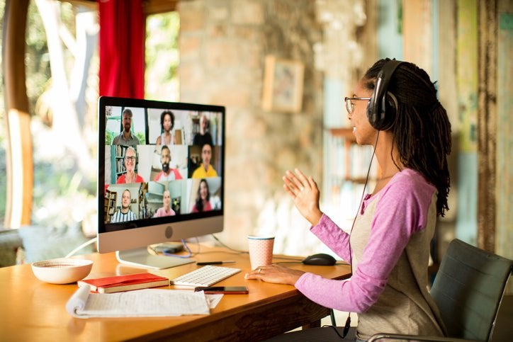 A woman smiles during an at-home video conference call for work.