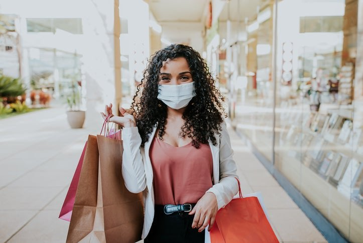Masked woman carrying various shopping bags.