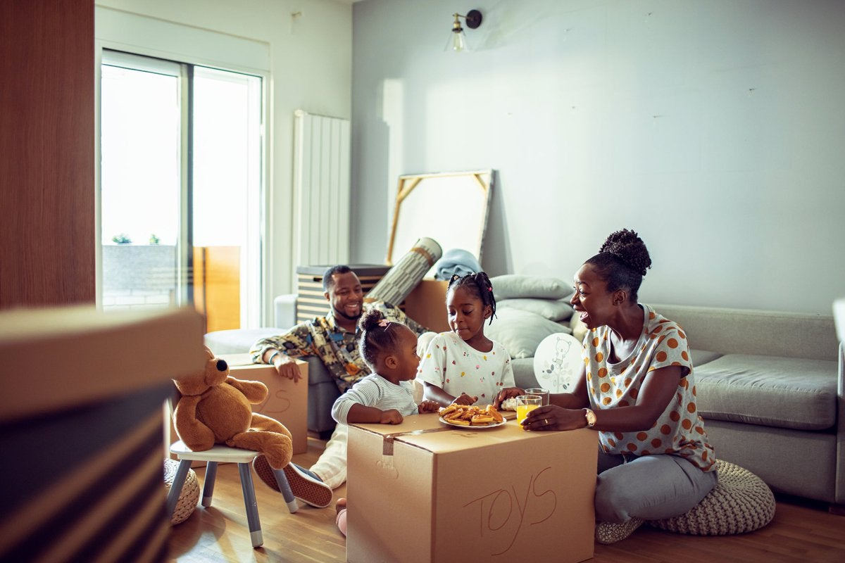 A family eats breakfast on top of cardboard moving boxes in their new home.