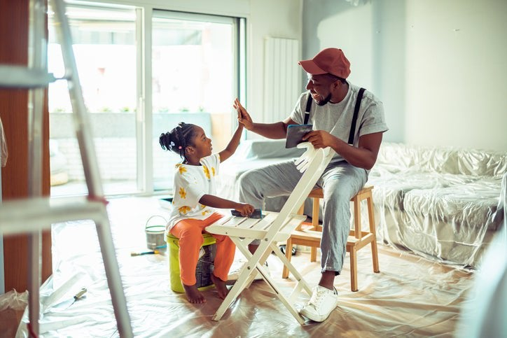 A father paints a chair with his daughter while remodeling their living room.