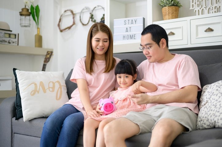 Couple sit on couch with their daughter holding a piggy bank.
