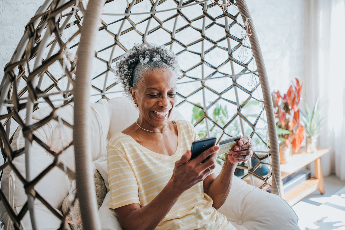 An older adult uses a credit card to make a payment on a smartphone in their living room.