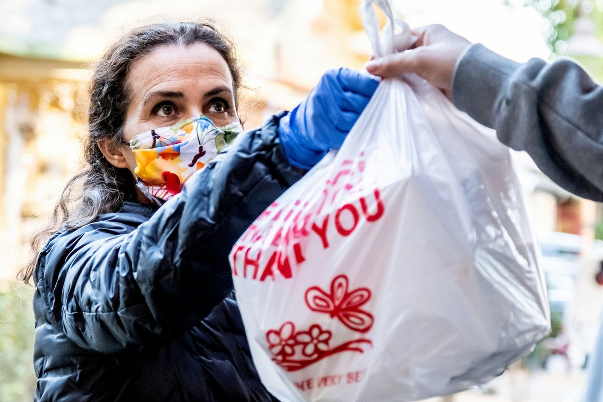 Woman hands off takeout order while wearing a mask and coat.