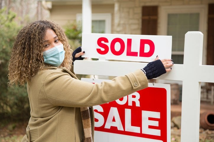 African American woman wearing a mask switches home For Sale sign to Sold.