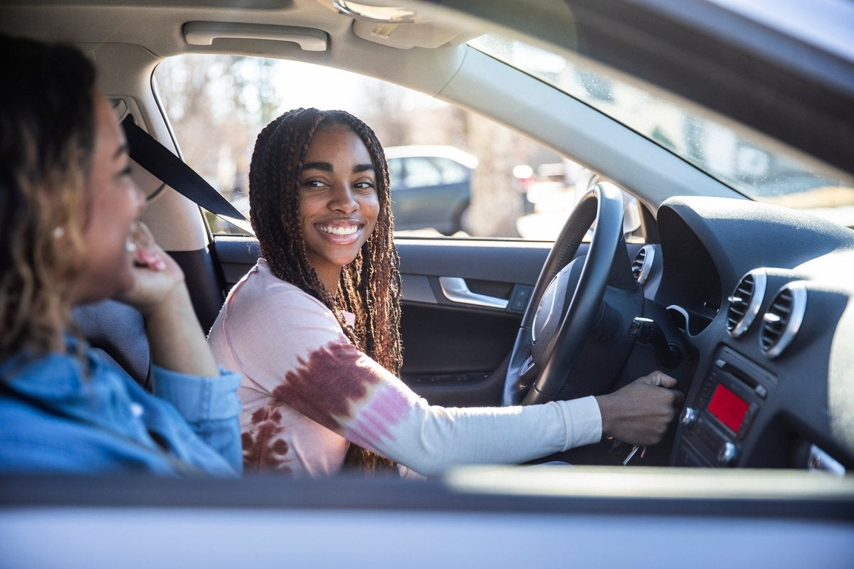 A teenager smiles at their mother as they turn on the car ignition.