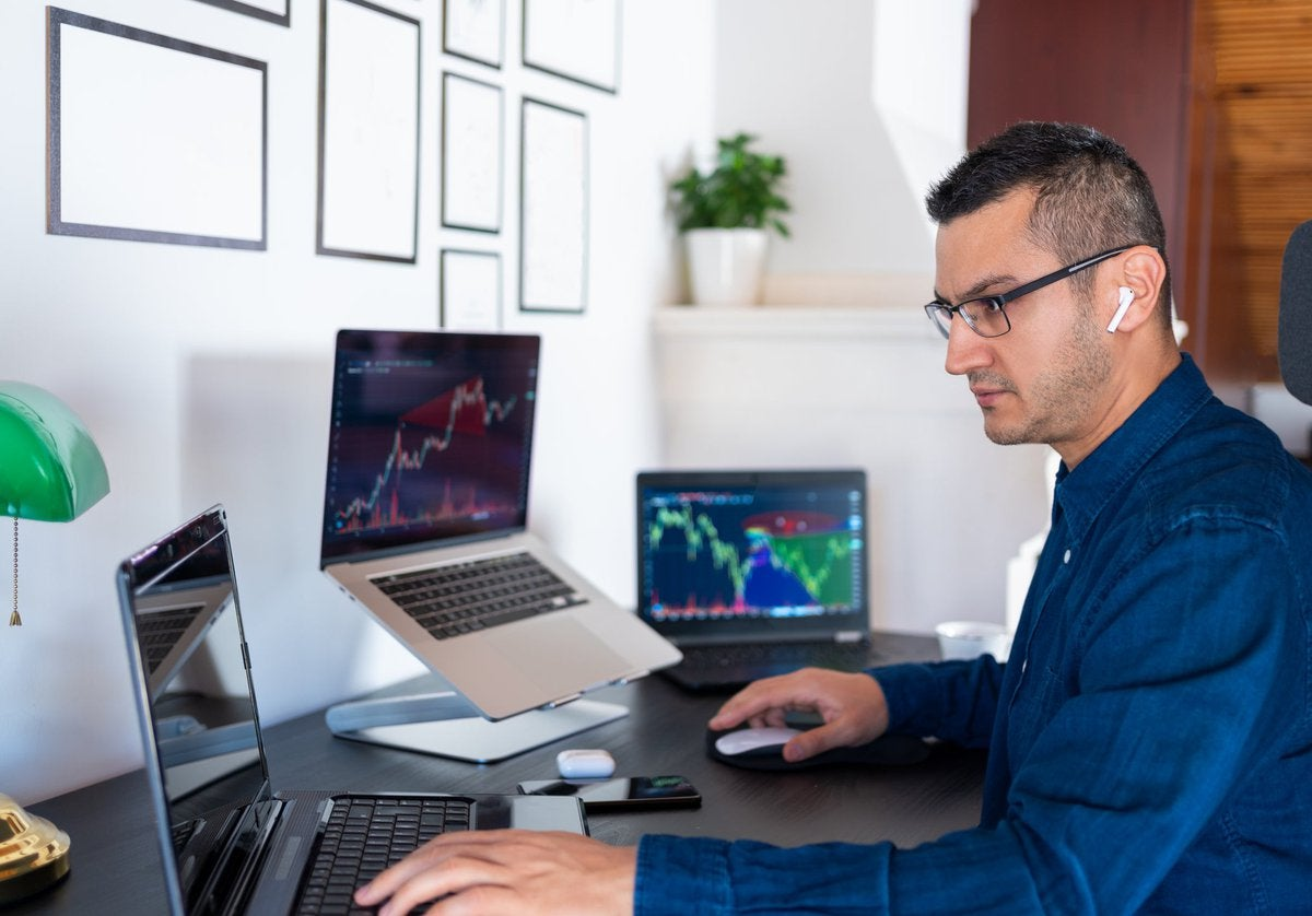 An investor analyzes the stock market with computer charts in their home office.