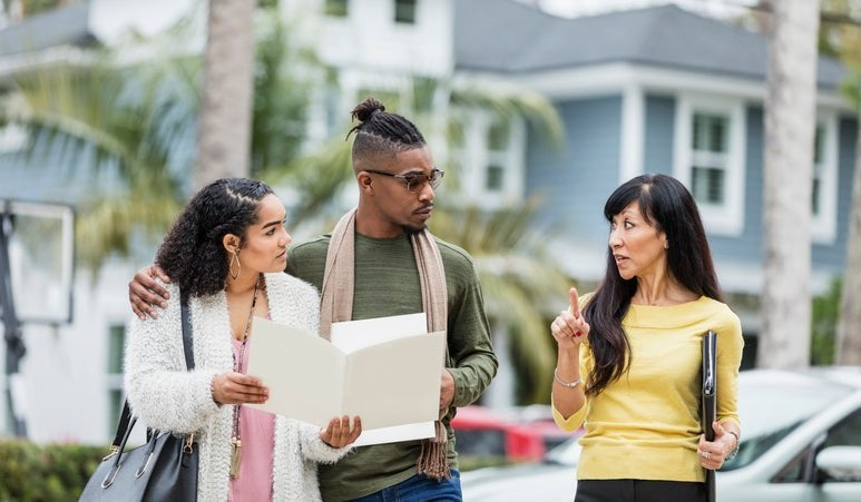 A real estate agent meeting in a parking lot with a young couple discussing mortgage documents.