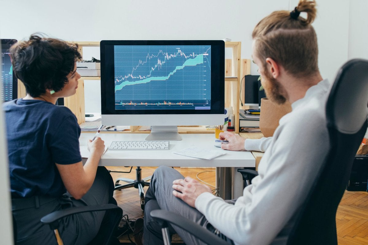 Two colleagues analyze a financial chart on a computer.