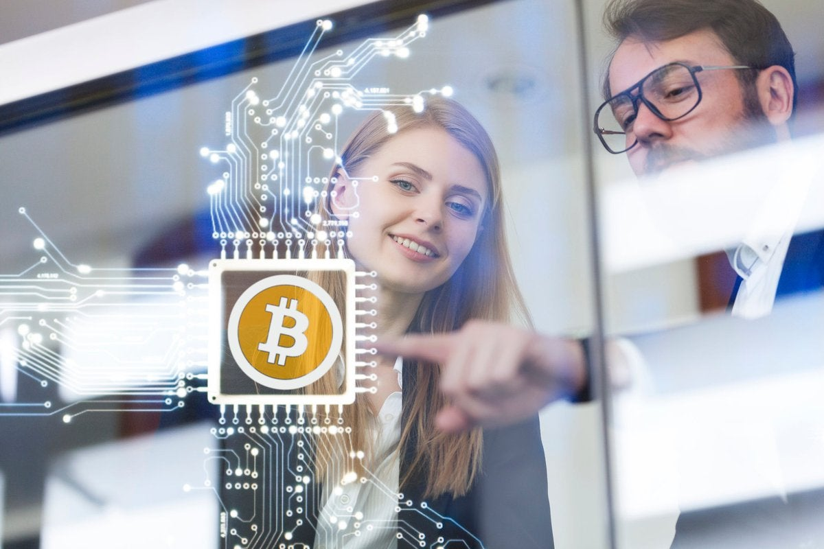 Business coworkers touch a cryptocurrency circuit on a virtual screen.