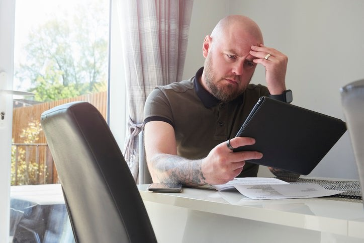 A homeowner looks worried as he reads through his household bills at the dining table.