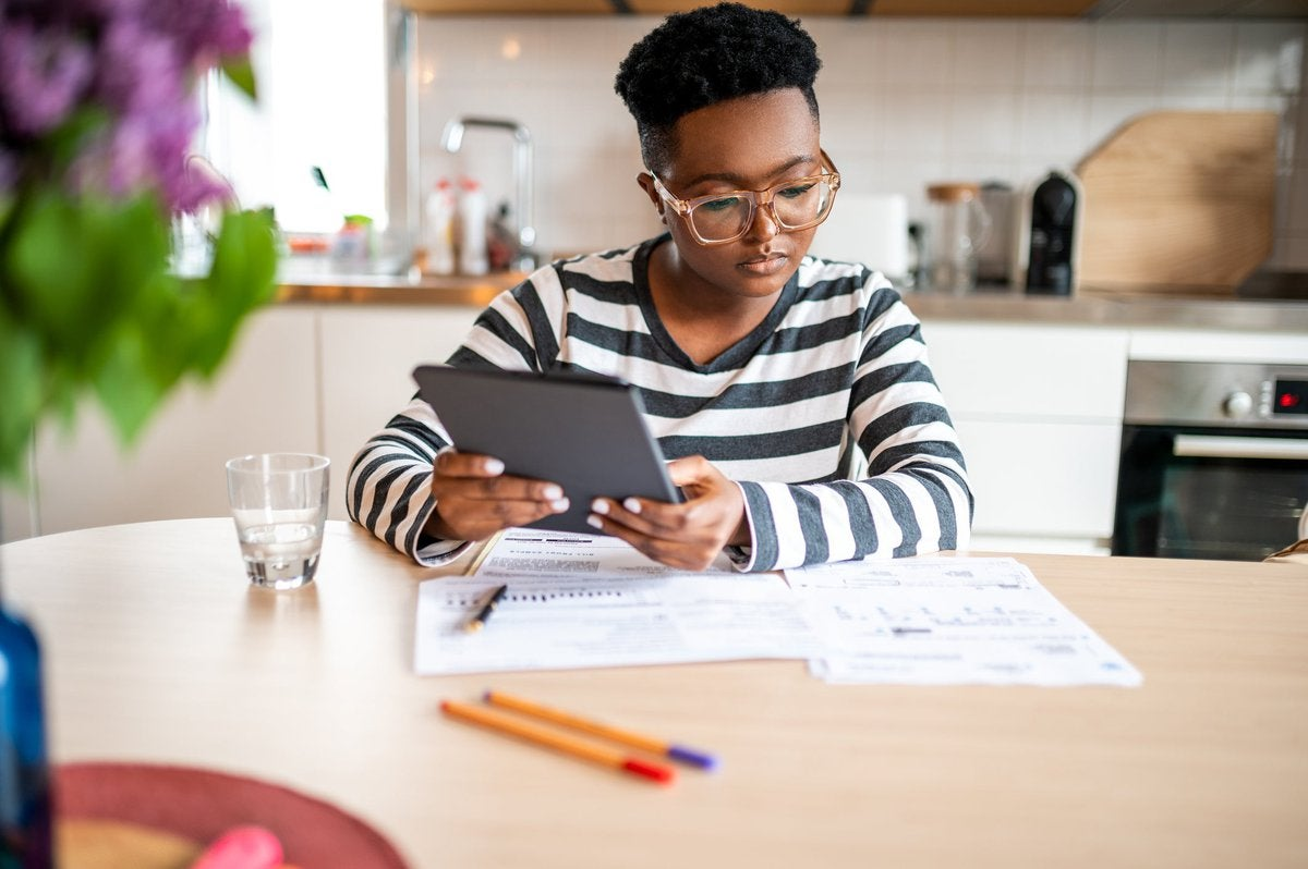 A person looks over paperwork and uses a tablet in their kitchen.