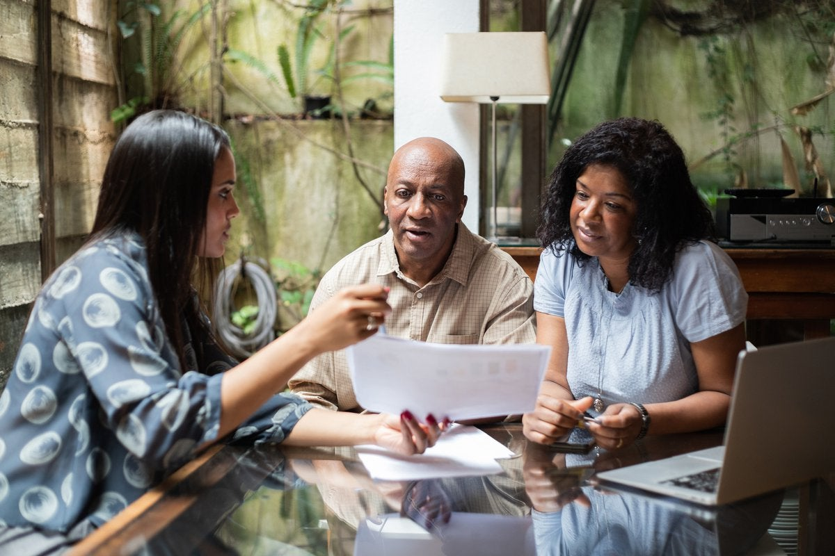A couple meets with a financial advisor in their home.