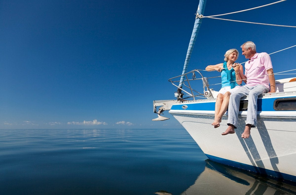 Smiling man and woman sitting on yacht