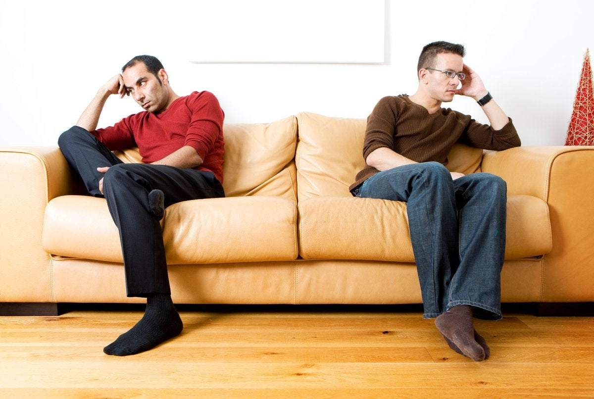 Two men sit on opposite ends of a couch, disgruntled.