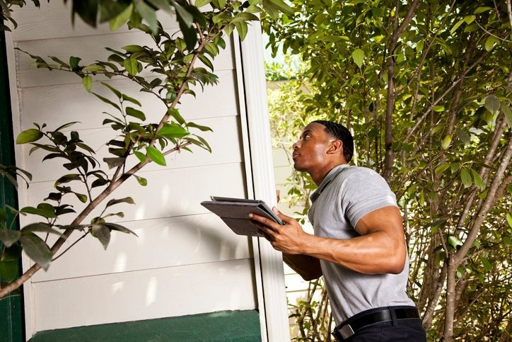 Home inspector checks the exterior walls of a house and uses a tablet to record results.