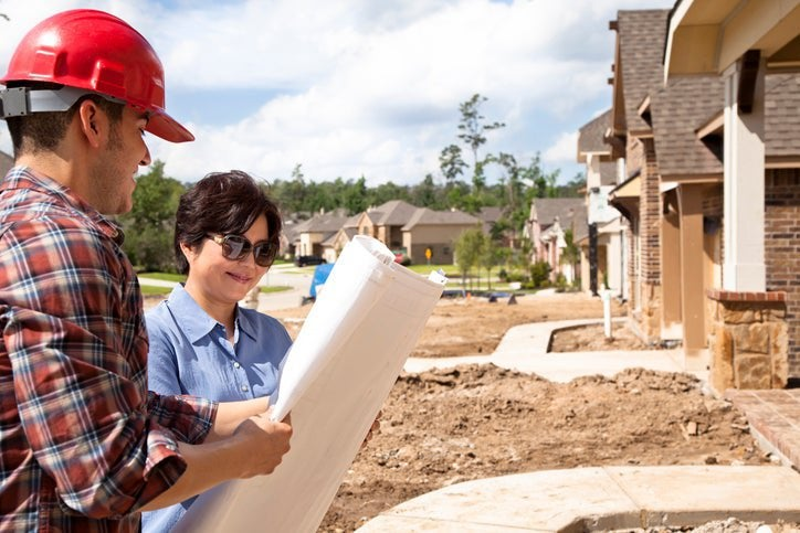 Builder talks to woman at her new home under construction.
