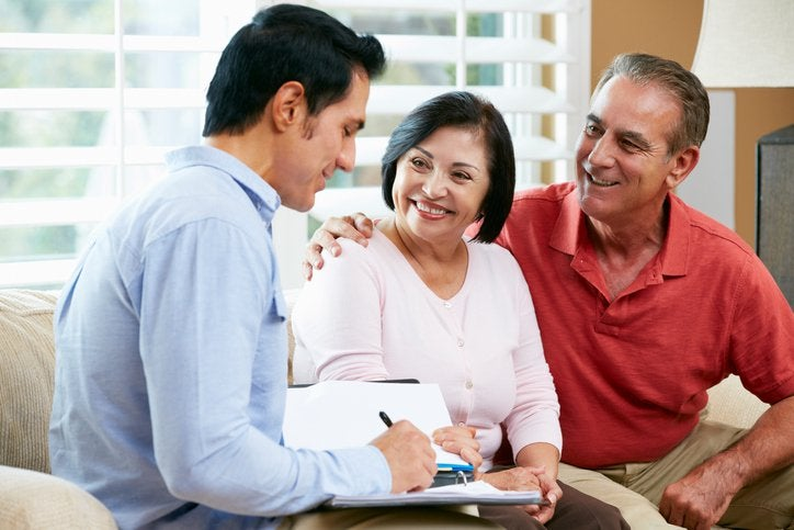 Smiling couple on sofa with salesperson finalizing paperwork.