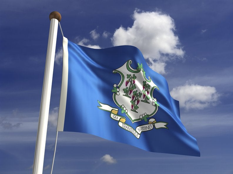 The Connecticut state flag flying in front of blue sky and white clouds.