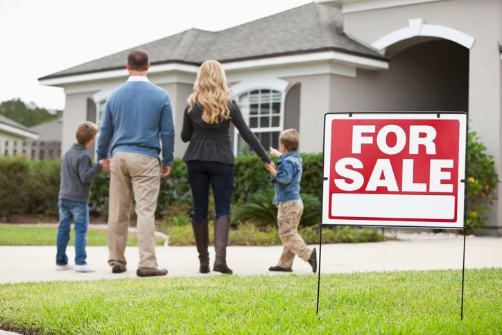 A family looks excitedly at a home with a For Sale sign on the lawn.