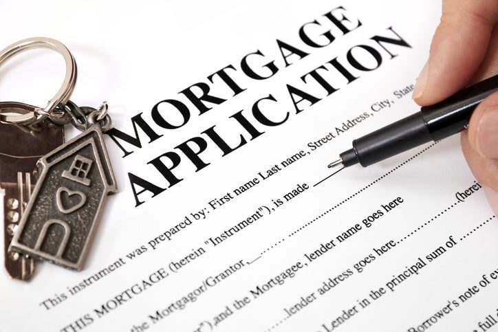 Close-up of someone about to fill out a blank mortgage application. A key ring of a house sits beside the pen.