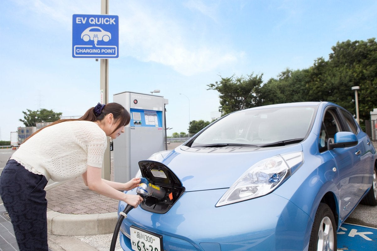A driver charges their electric car at an outside charging port.