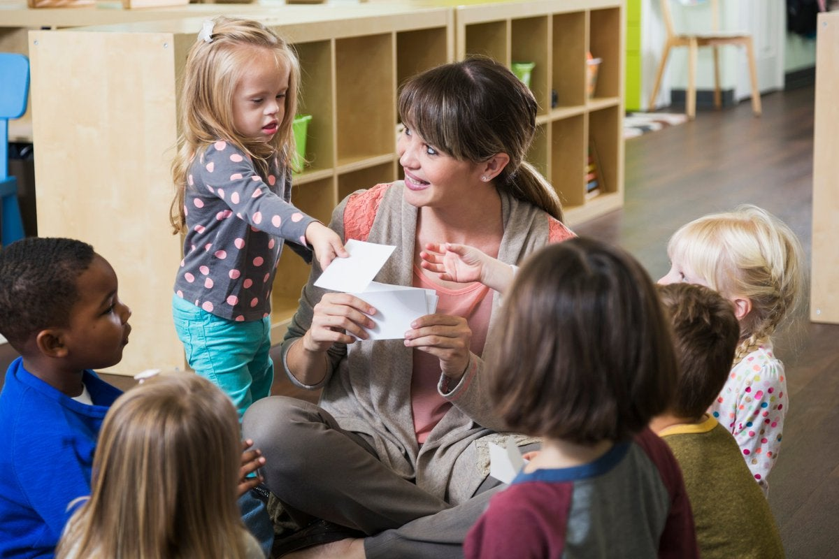 A pre-school leader sits with a group of children in a classroom, holding up flash cards.