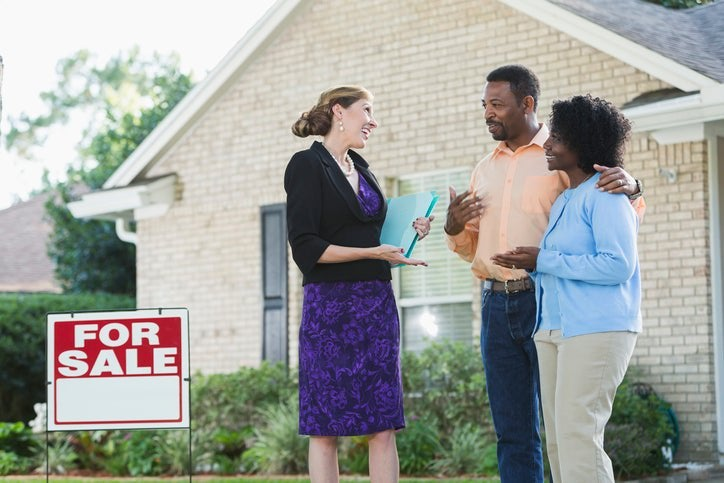 Couple speaks with real estate agent in front of a house that's for sale