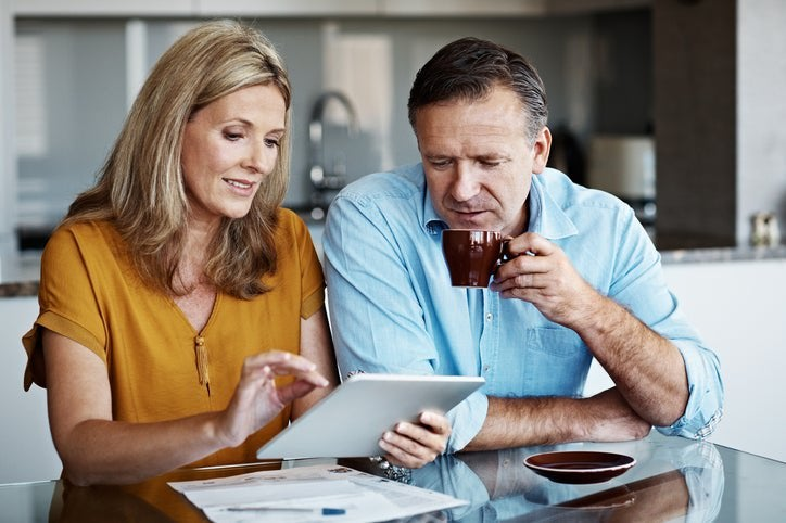 A mature couple goes over financial paperwork at home.