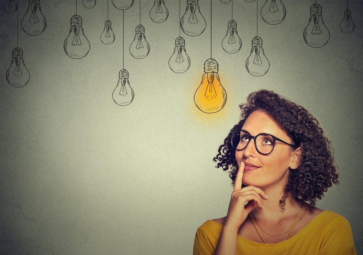 Woman in glasses looking up at drawings of many light bulbs, only one of which is lit up.