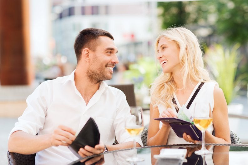 Young couple beaming at each other while taking care of the bill together at a restaurant.