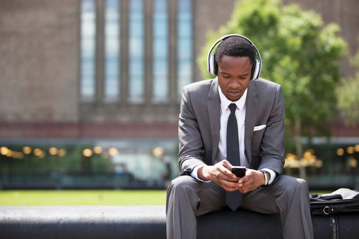 man in suit wearing headphones and looking at phone