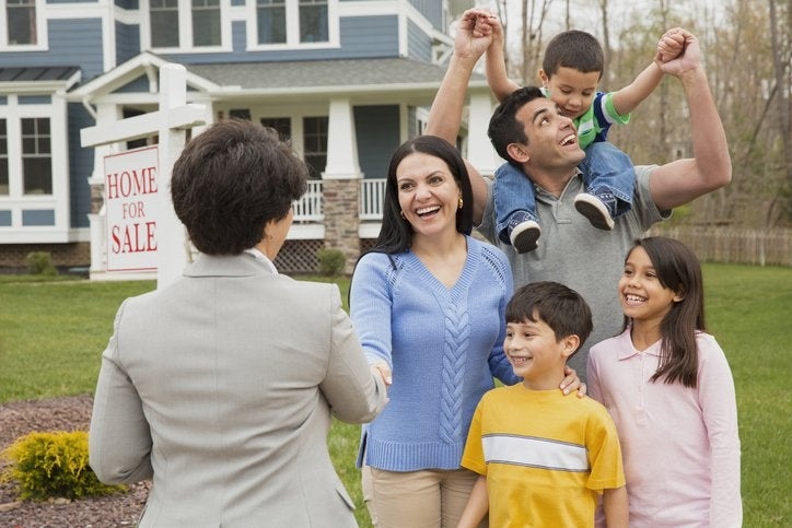 """A parent shakes hands with a realtor as their family celebrates. A house with a sign that reads """"Home for Sale"""" is behind them."""