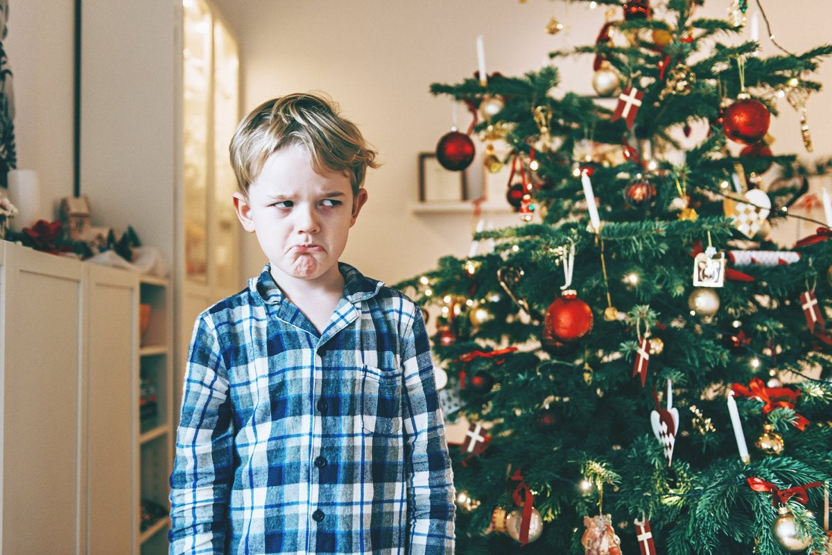 Grumpy child giving Christmas tree the side-eye.