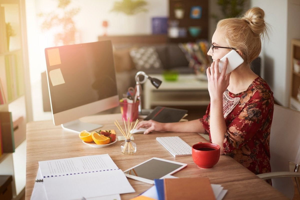 Young woman at home office desk using her cell phone.