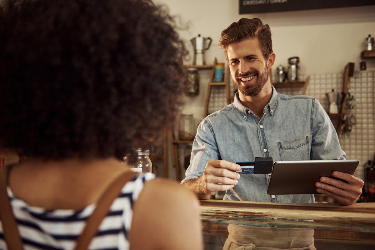 Barista grinning at customer as he swipes her card through an iPad reader.