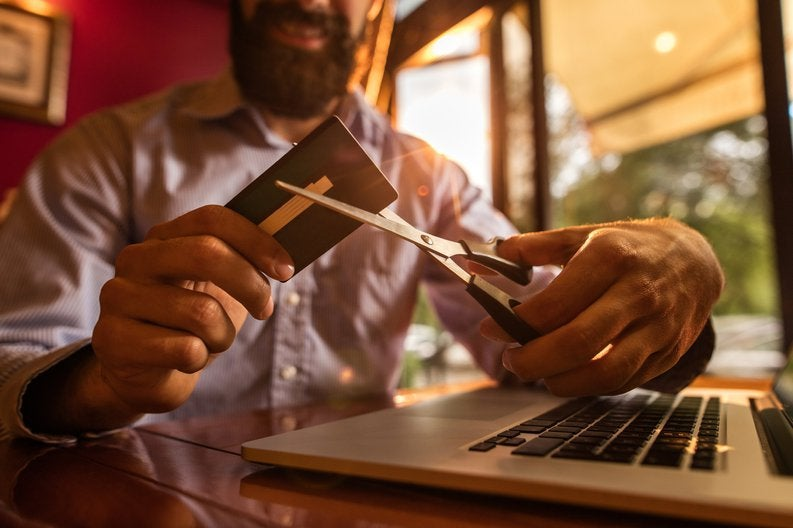 Man with massive beard cutting up credit card with pair of scissors.